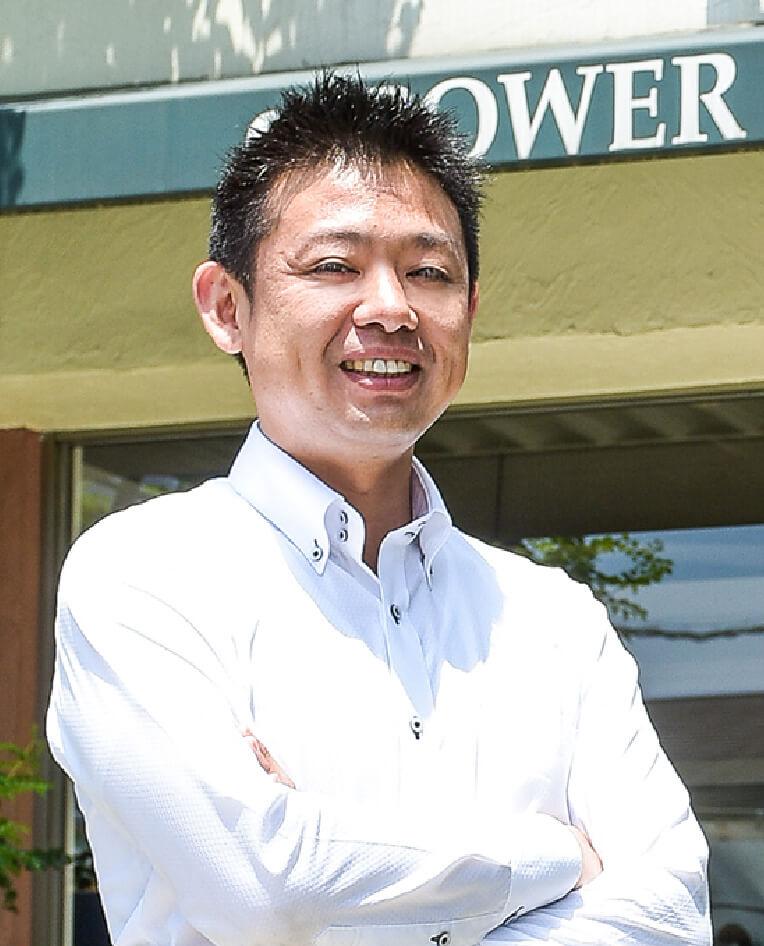 パワーハウス株式会社 代表取締役社長 井村 優介が腕を組んで笑っている写真